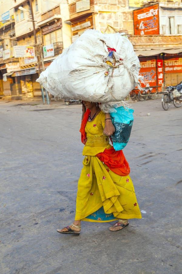 De Indische vrouw draagt zware lading stock foto
