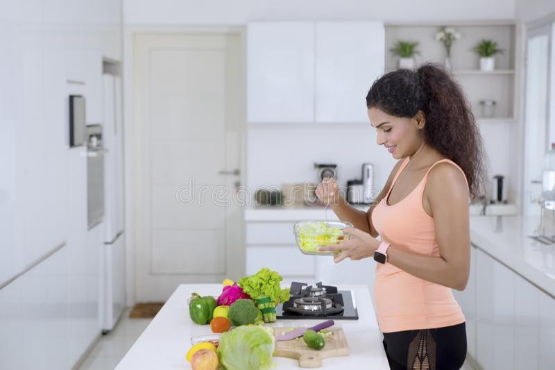 De Indische vrouw eet verse salade in de keuken stock foto's