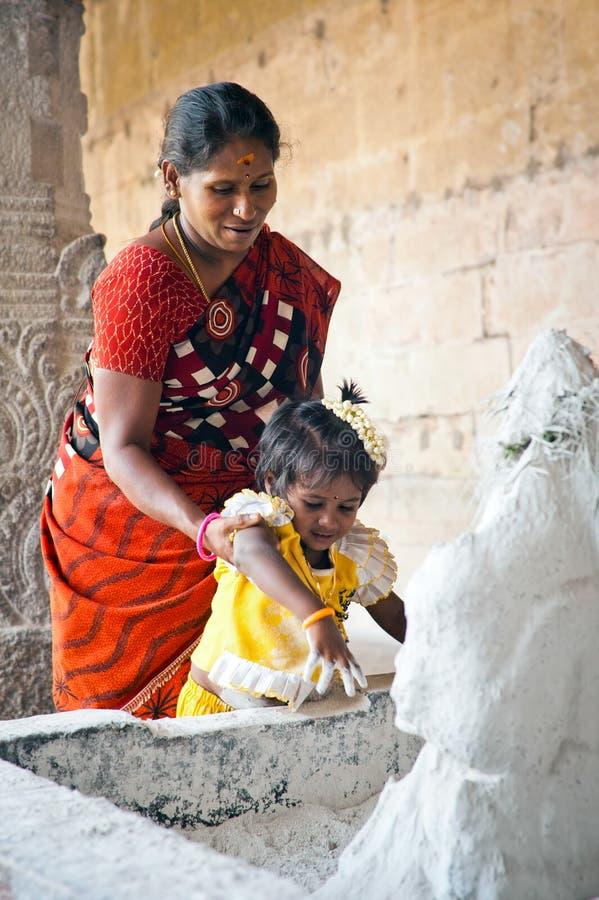 De Indische vrouw en het kind brengen Hindoes godsdienstig dienstenaanbod royalty-vrije stock fotografie
