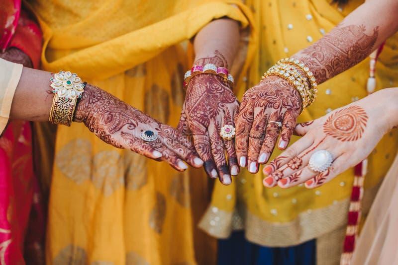 De Indische vrouw houdt haar die handen met mehndi worden behandeld en het dragen van bustehouder stock foto