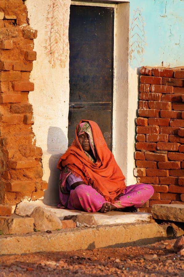 De Indische vrouw in oranje Sari zit op een huisportiek royalty-vrije stock afbeelding