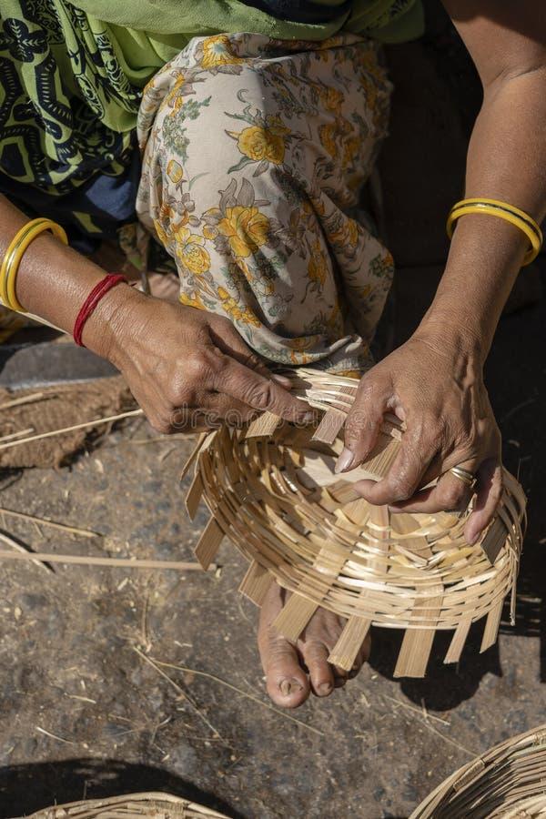 De Indische vrouw weeft een bamboemand met haar benen en de wapens in een markt, sluiten omhoog India stock afbeelding