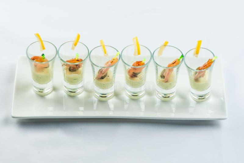 De individuele Cocktailgarnalen schoten glazen met heerlijke eigengemaakte tandsteen kruidige die saus met peterselieblad wordt v stock foto's
