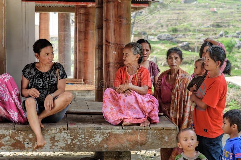 De Indonesische vrouwen zitten onder de vloer van tongkonan traditioneel huis in Tana Toraja stock afbeeldingen