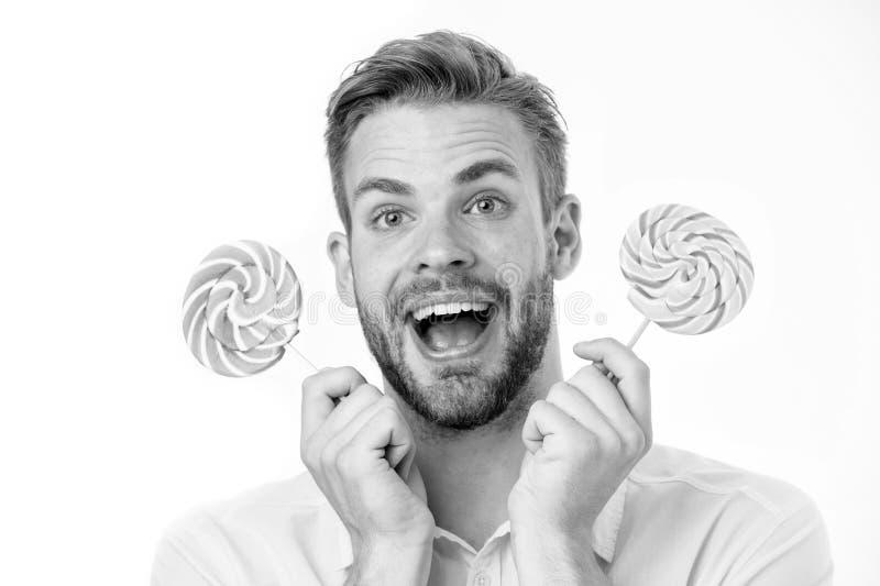 De indrukwekkende voeding van de feitensuiker Houdt de mensen knappe gebaarde kerel lollysuikergoed De mens met lolly kijkt verra stock fotografie