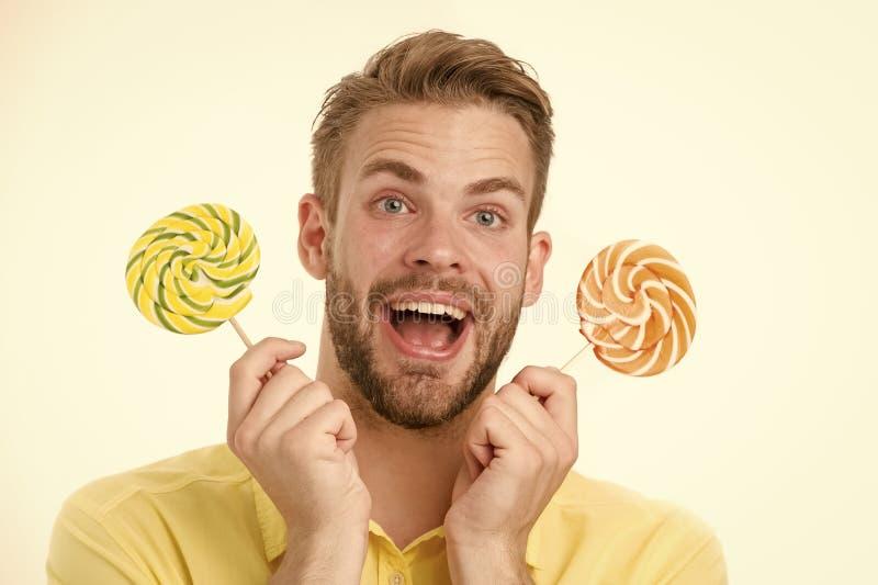 De indrukwekkende voeding van de feitensuiker Houdt de mensen knappe gebaarde kerel lollysuikergoed De mens met lolly kijkt verra royalty-vrije stock fotografie