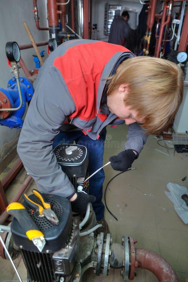 De industriële Diensten van de Pompreparatie, de technicus verbindt een moto stock foto