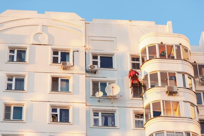 De industriële klimmer bevestigde op veiligheidskabels die en voorgevel van het voortbouwen op zonnige dag puttying schilderen B stock fotografie