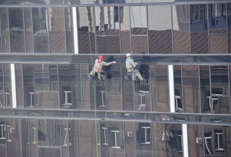 de industriële klimmers maken vensters schoon stock afbeelding
