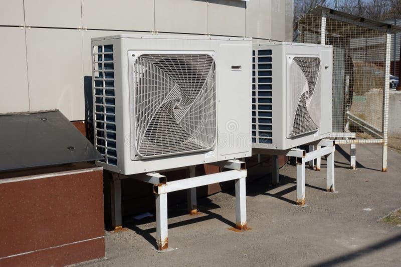 De industriële openluchteenheid van airconditionercondensatoren ter plaatse dichtbij het gebouw op een hete de zomerdag stock foto