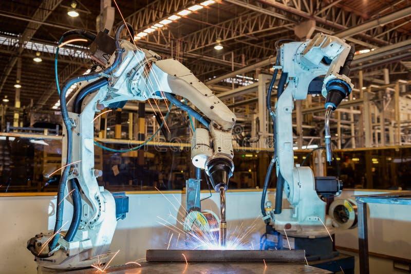 De industriële robot last het deel van het assemblagestaal in autofabriek stock afbeeldingen