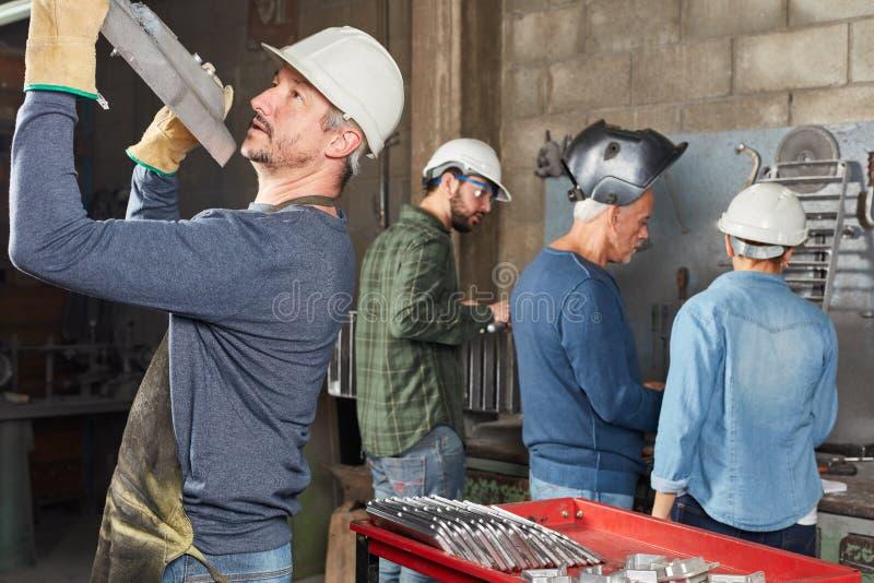 De industriearbeider het controleren metallurgiecomponent stock foto's
