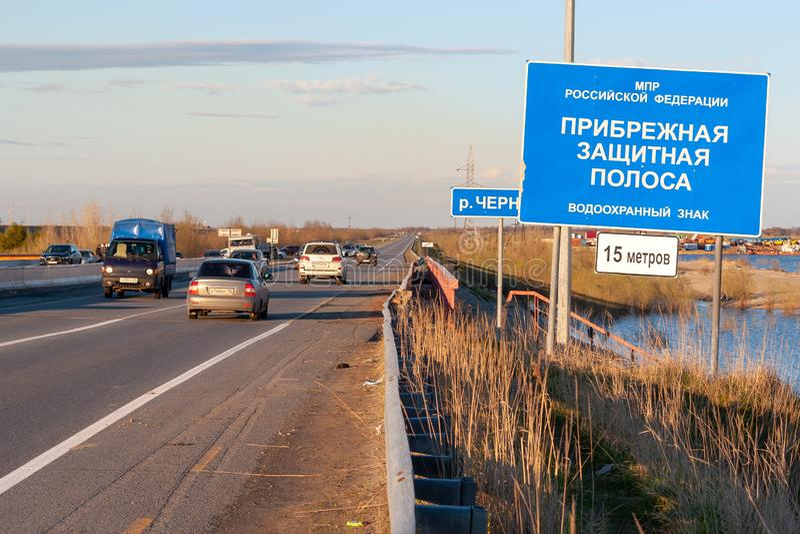 De informatieraad met de inschrijving-kust beschermende strook, installeerde op de weg, naast de rivier royalty-vrije stock foto