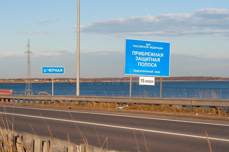 De informatieraad met de inschrijving-kust beschermende strook, installeerde op de weg, naast de rivier royalty-vrije stock foto's