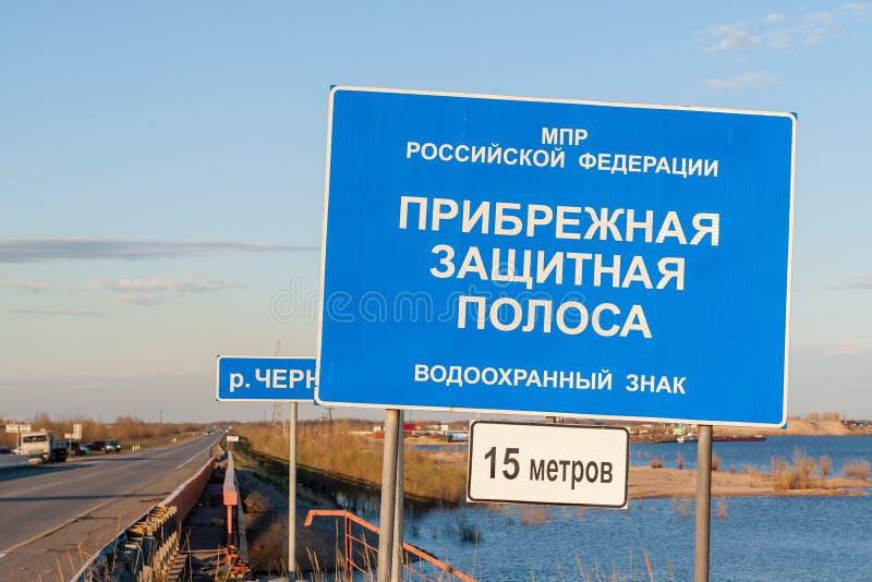 De informatieraad met de inschrijving-kust beschermende strook, installeerde op de weg, naast de rivier stock fotografie