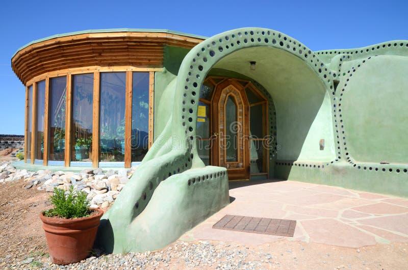 De ingang van een duurzaam huis van Earthship maakte uit adobe en upcycled glasflessen dichtbij Taos in New Mexico, de V.S. stock afbeeldingen