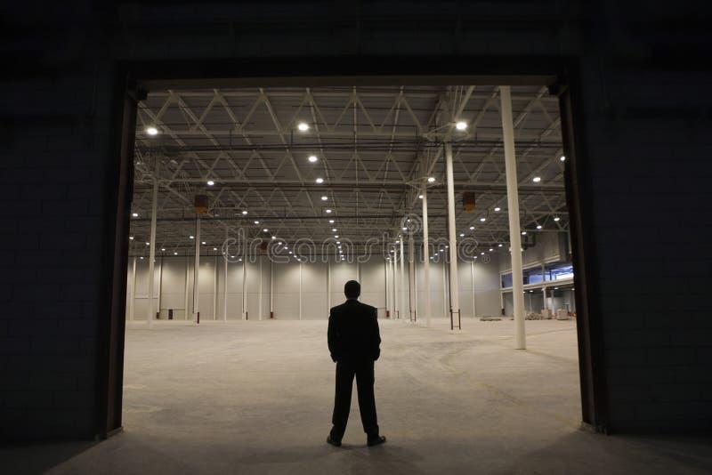 De Ingang van zakenmanstanding at warehouse royalty-vrije stock fotografie