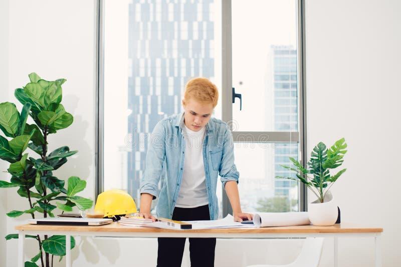 De ingenieur of de architect in blauwe trui werken aan constructio royalty-vrije stock afbeelding