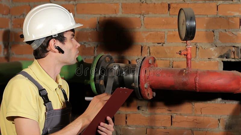 De ingenieur controleert de manometerlezing De arbeider registreert de lezingen van de apparaten in het klembord Knap stock footage