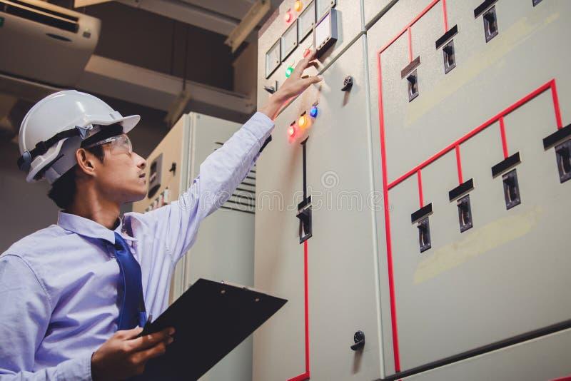 De ingenieur is controlevoltage of stroom door voltmeter in controlebord van elektrische centrale royalty-vrije stock afbeelding
