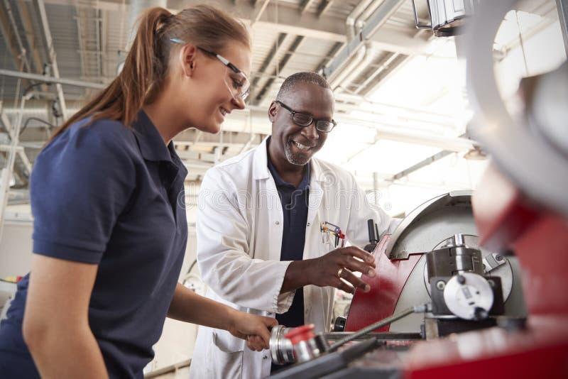 De ingenieur die vrouwelijke leerling tonen hoe te om machines in werking te stellen, sluit omhoog stock foto