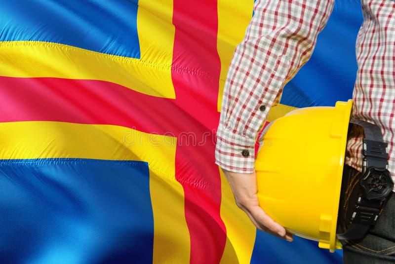 De ingenieur houdt gele veiligheidshelm met de golvende Aland-achtergrond van de Eilandenvlag Bouw en de bouwconcept royalty-vrije stock afbeeldingen