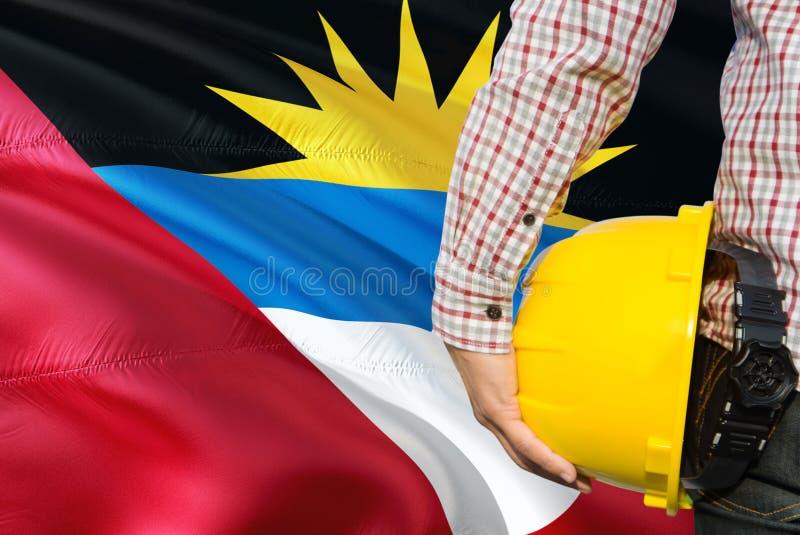De ingenieur houdt gele veiligheidshelm met het golven Antigua en de vlagachtergrond van Barbuda Bouw en de bouwconcept royalty-vrije stock afbeelding