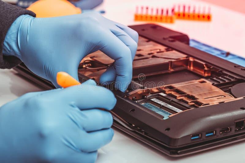 De ingenieur ontmantelt de details van gebroken laptop voor reparatie royalty-vrije stock afbeeldingen
