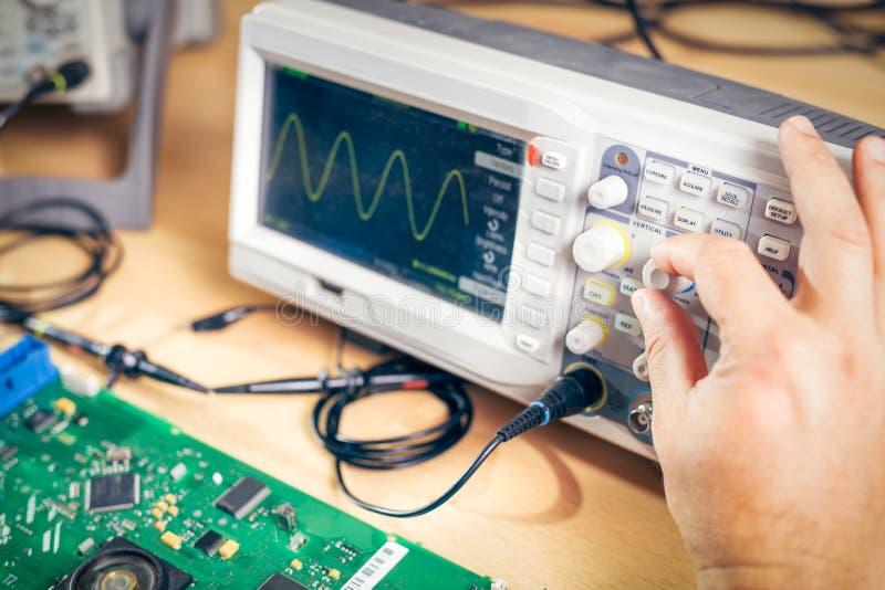 De ingenieur test elektronische componenten met oscilloscoop in het de dienstcentrum royalty-vrije stock foto