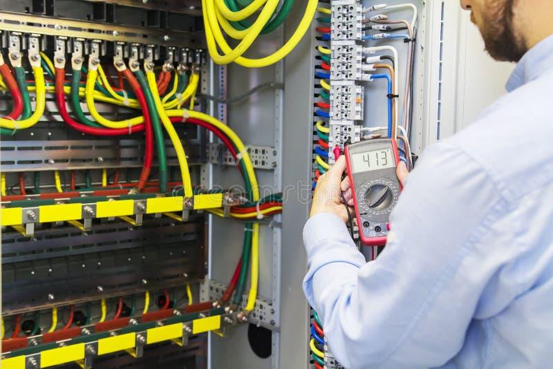 De ingenieur test de kringsdoos in drie stadia van de machtshoogspanning met multimeter Het elektrische systeem van de de dienstm royalty-vrije stock foto