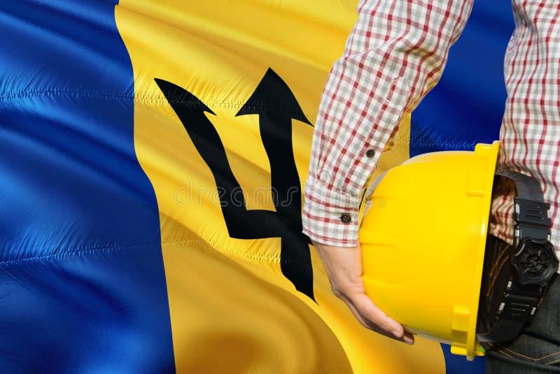 De Ingenieur van Barbados houdt gele veiligheidshelm met golvende de vlagachtergrond van Barbados Bouw en de bouwconcept stock fotografie