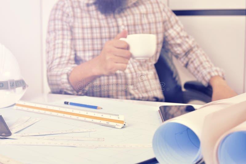 De ingenieur werkt aan het bureau met tekeningsplan stock fotografie