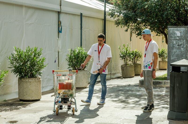 De ingenieurs, ontwikkelaars testen hun uitvinding - karretjeproducten van de supermarkt die de robot zelf drijft stock foto