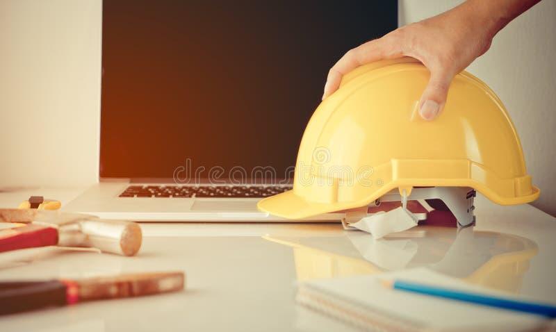 De ingenieursarbeider, bouwvakker, reparatiemens neemt veiligheidshelm op stock foto