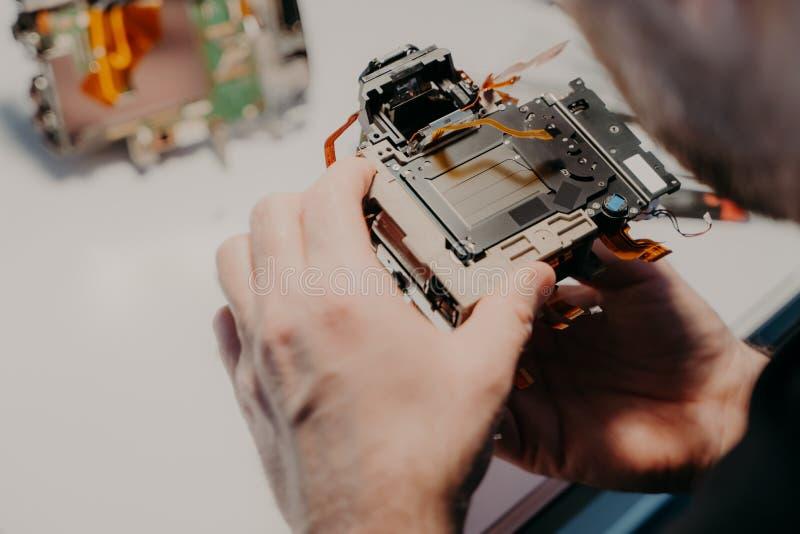 De ingenieurshanden houdt gebroken fotocamera, stelt tegen werkruimte, herstelt digitaal apparaat of professionele dslrcamera royalty-vrije stock foto's