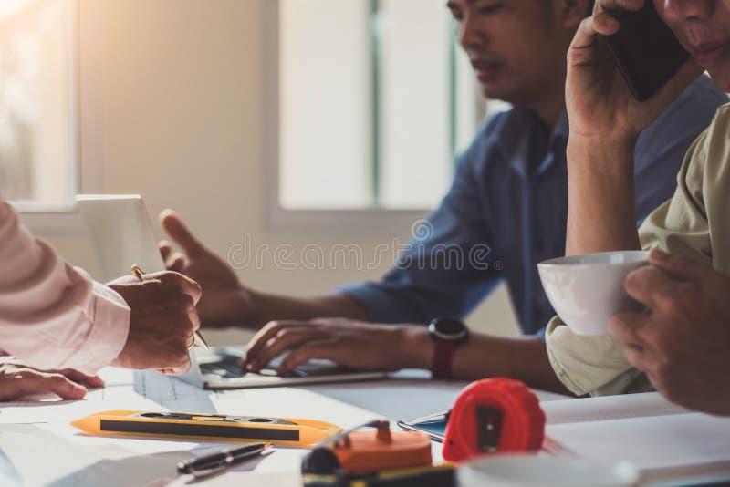 De ingenieursontwerp die van de teamarchitect met blauwdruk op lijst in het bureau bespreken Van de techniekhulpmiddelen en bouw  stock foto's