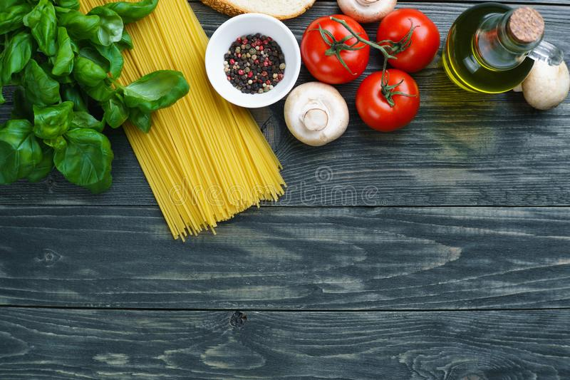 De ingrediënten van deegwaren Ruwe spaghetti, tomaten, basilicum, olijfolie, mu stock fotografie