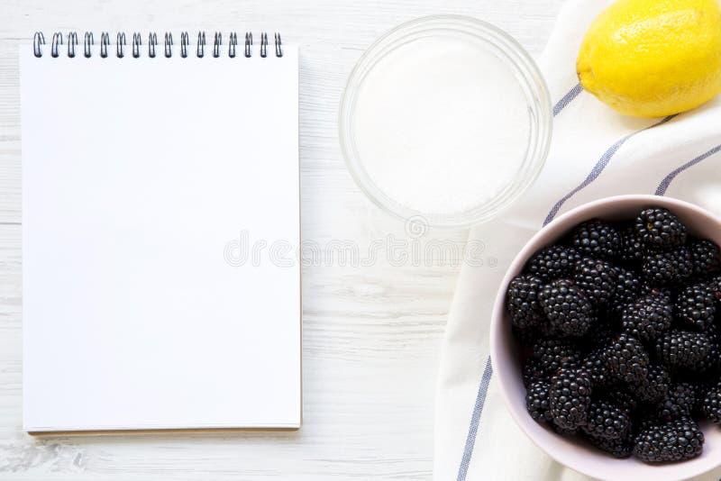 De ingrediënten voor braambessen blokkeren met leeg notitieboekje op witte houten lijst, hoogste mening stock fotografie