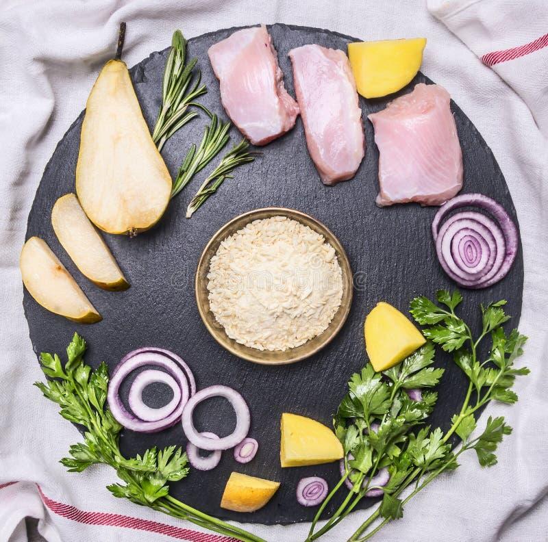 De ingrediënten voor het koken van de borst van Turkije met peer, rijst, kruiden en groenten worden opgemaakt op ronde scherpe ra royalty-vrije stock afbeelding