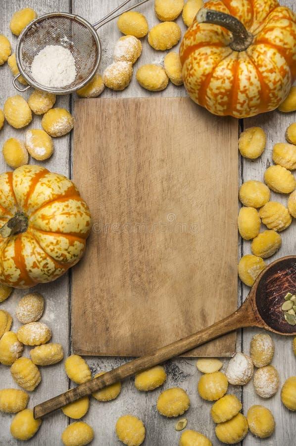 De ingrediënten voor het koken van de bloem van pompoengnocchi zeven de amandelenpompoen van de bloem houten lepel, houten scherp royalty-vrije stock fotografie