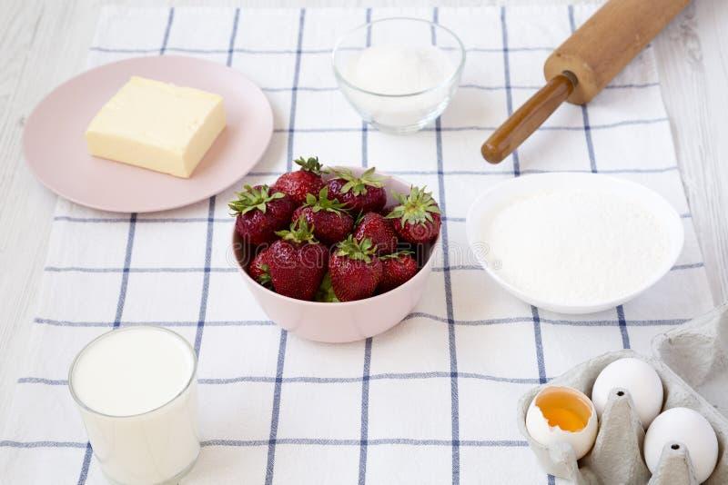 De ingrediëntenbloem van de aardbeipastei, eieren, boter, melk, suiker, aardbei, zijaanzicht Kokende aardbeipastei of cake stock afbeelding