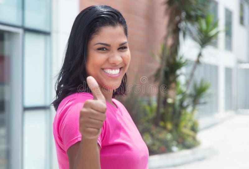 De inheemse Latijnse vrouw in een roze overhemd is gelukkig in stad stock fotografie