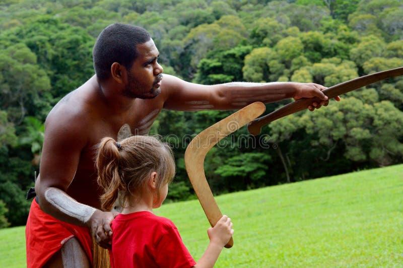 De inheemse mens van Australiërs onderwijst een jong meisje hoe te om B te werpen royalty-vrije stock afbeelding
