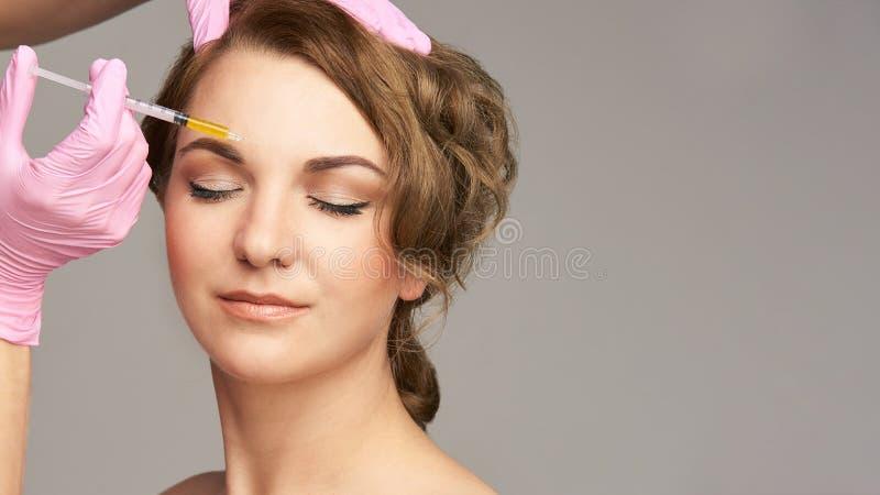 De injectie van de gezichtsnaald De jonge procedure van de vrouwenkosmetiek Artsen roze handschoenen brow royalty-vrije stock foto