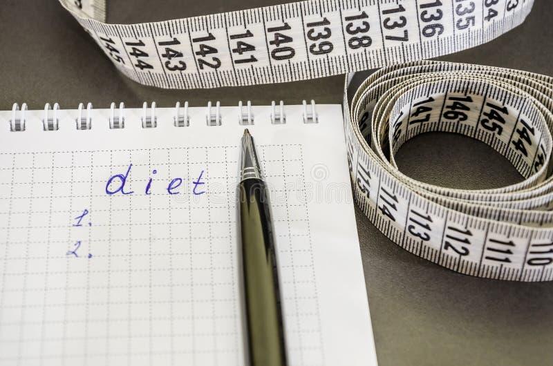 De inschrijving 'dieet 'op een notitieboekje en een pen op een zwarte achtergrond royalty-vrije stock foto