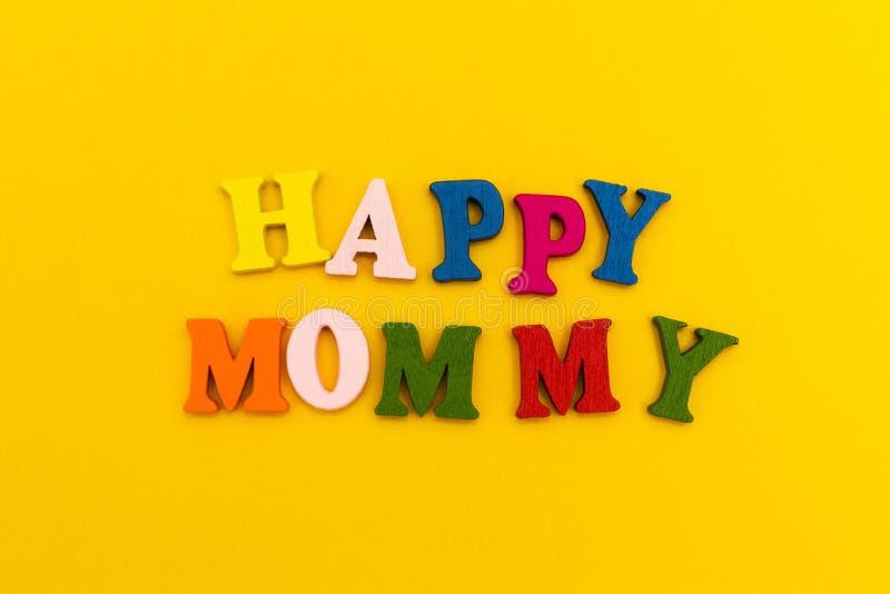 De inschrijving 'Gelukkige Mama 'in kleurrijke brieven op een gele achtergrond stock afbeeldingen