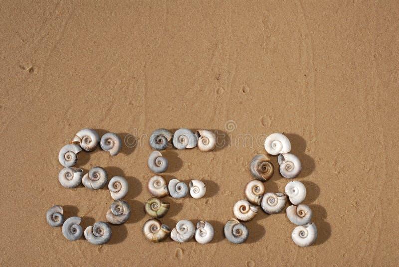 De inschrijving 'Overzees 'wordt geschreven door kleine overzeese shells op het gele zand stock foto