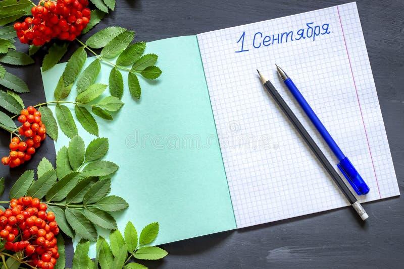 De inschrijving in Russisch 1 september in een notitieboekje met bladeren en lijsterbessenbessen op een zwarte achtergrond stock foto