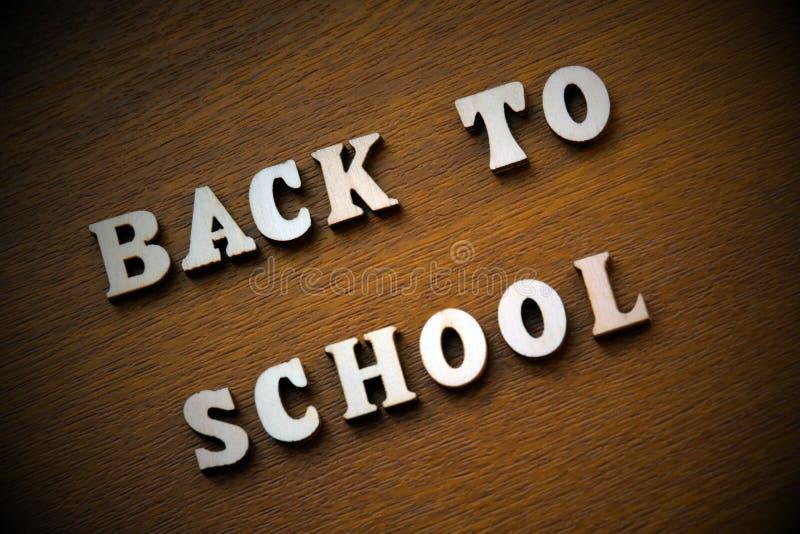 De inschrijving terug naar school van houten brieven op een bruine achtergrond wordt opgemaakt die vignetting royalty-vrije stock foto's