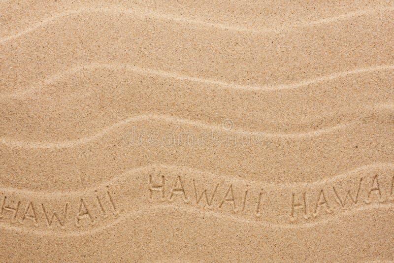 De inschrijving van Hawaï op het golvende zand stock afbeelding
